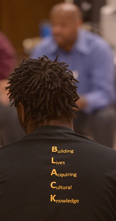 photo of african american student wearing shirt with acronym 'BLACK' - Building Lives Acquiring Cultural Knowledge
