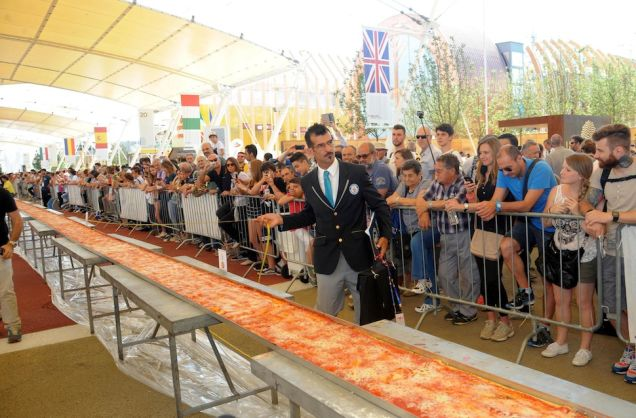 Officially measuring the candidate for the World's Longest Pizza (Source: JEZEBEL)