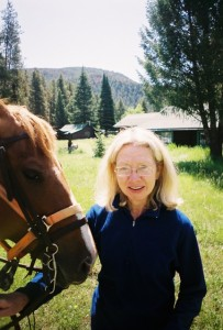 Jane Van Dyk with horse and cabins