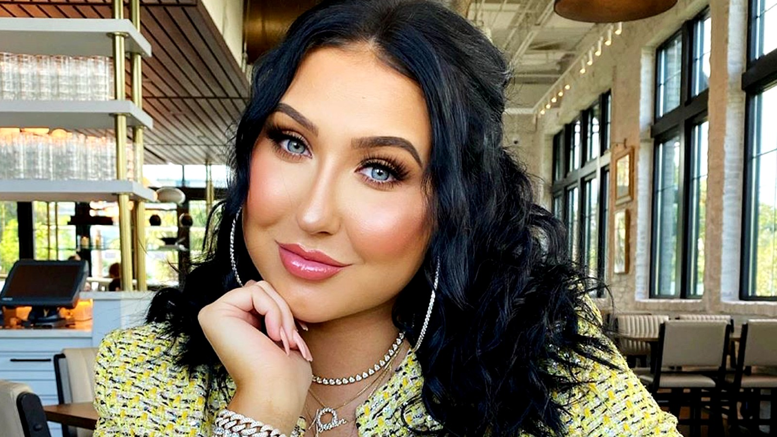 Jaclyn Hill poses with her head on her hand sitting down