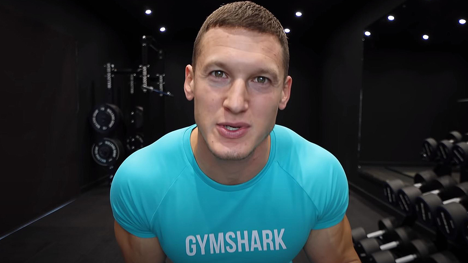 MattDoesFitness talks to his audience while sitting in his home gym.