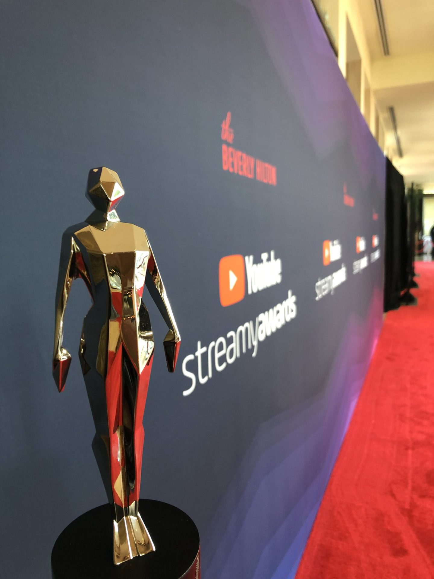 A photo of a Streamy Award trophy on the red carpet.
