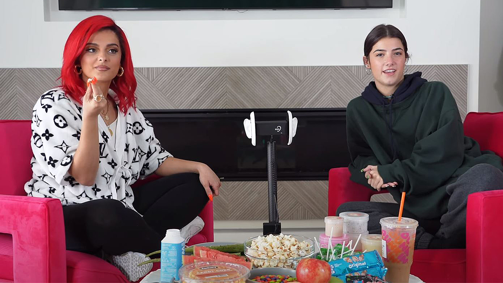 Charli D'Amelio and Bebe Rexha sit in front of a spread of candy and an ASMR mic.
