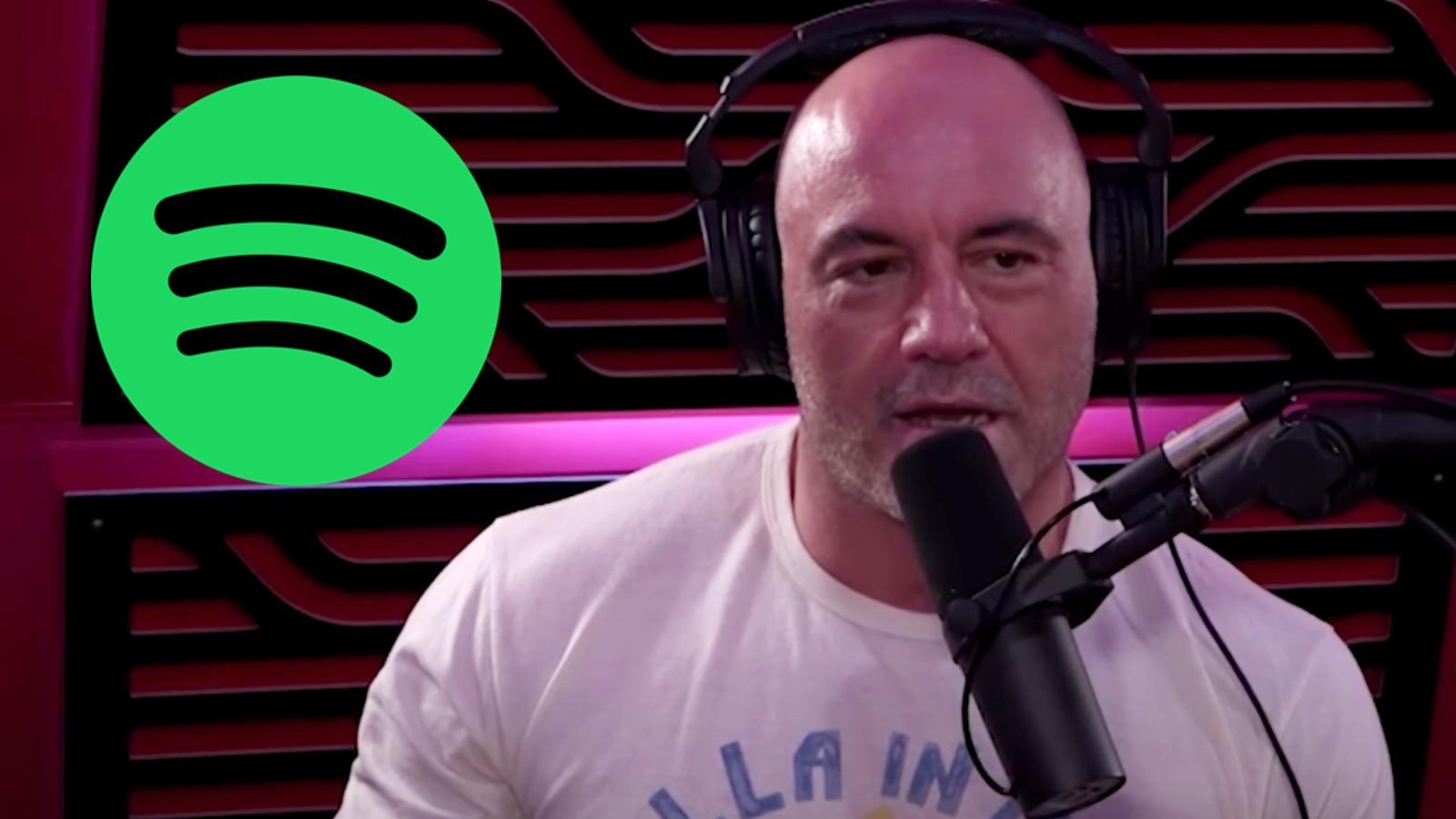 Joe Rogan in his podcast studio next to the Spotify logo