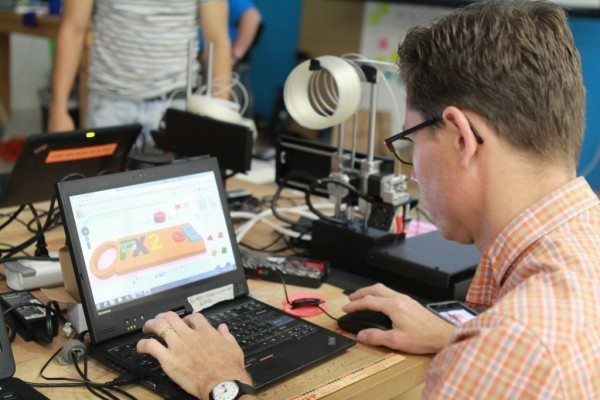 Attendee working with design software and a 3D printer during DHF's 3D Printing for Educators Workshop