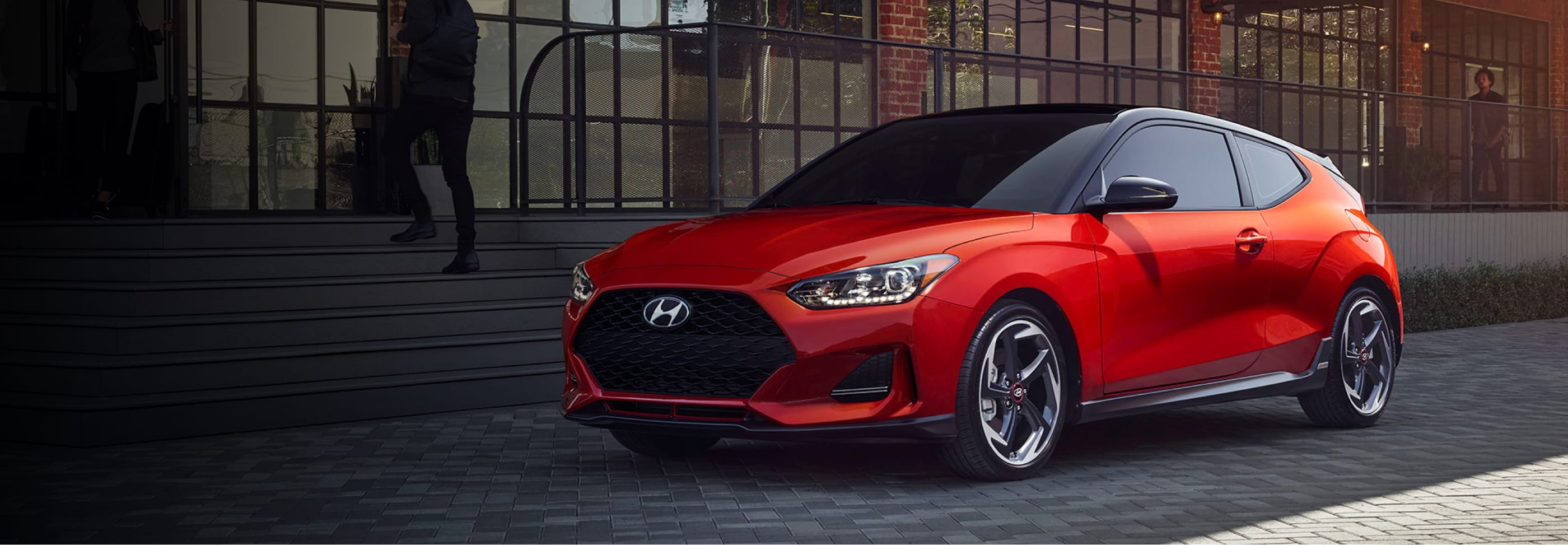A red 2020 Hyundai Veloster parked outside of a building