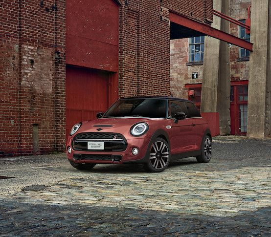 The MINI COOPER HARDTOP CORAL RED EDITION parked on a cobblestone road.