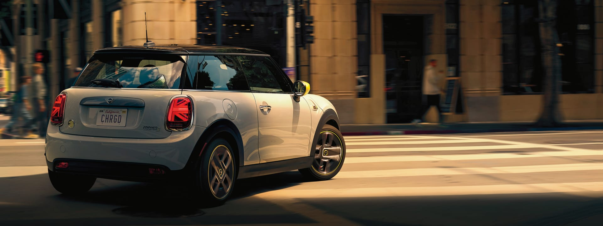 MINI Electric Hardtop 2 Door – white silver with yellow trim and black hardtop driving on street.