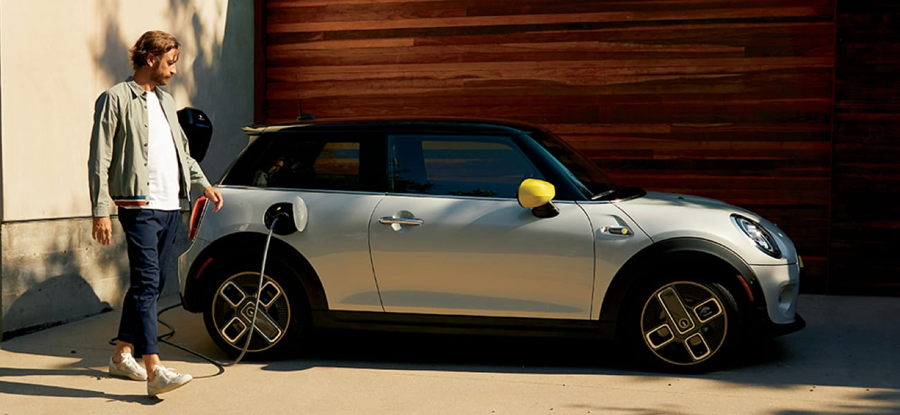 MINI Electric Hardtop 2 Door – white silver with yellow trim being charged by a man.