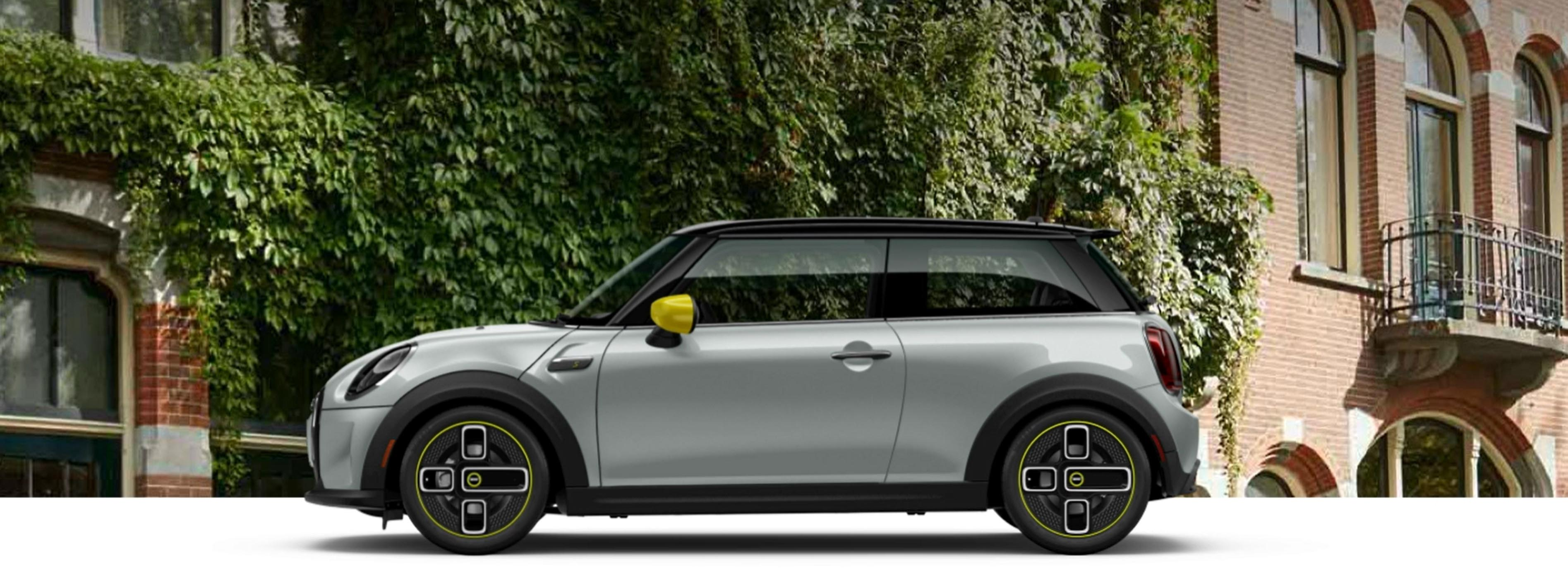 MINI MINI Electric Hardtop 2 Door – white silver with yellow trim and black hardtop parked in front of house.