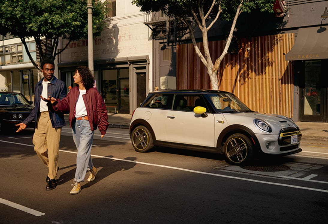 MINI Electric Hardtop 2 Door – white silver with yellow trim parked on street with couple walking in front.
