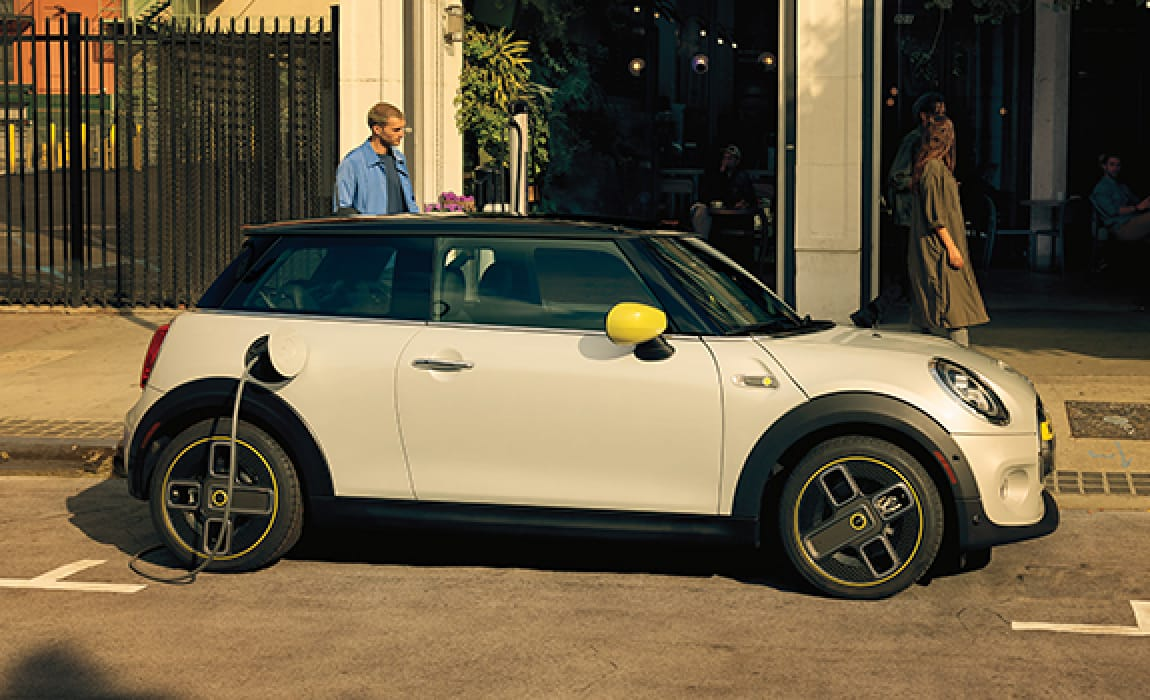 MINI Electric Hardtop 2 Door – white silver with yellow trim parked on street with man behind car.
