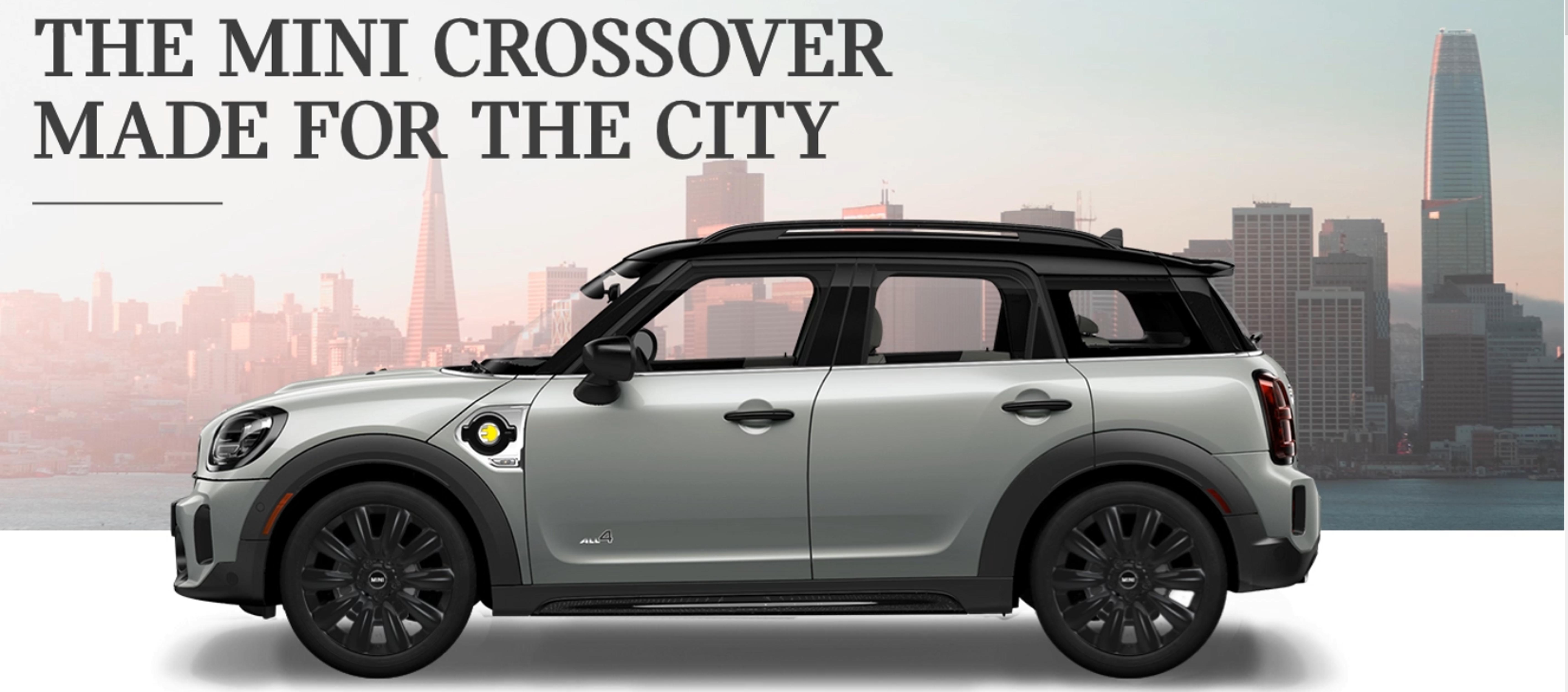 MINI The MINI Cooper SE Countryman PHEV parked in front of a city scape.