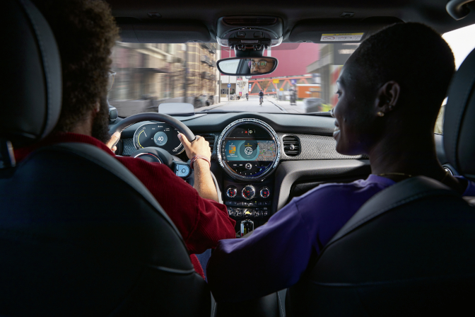 A look over the right shoulder of a couple driving their 2022 MINI Cooper SE Hardtop 2 Door around the city.
