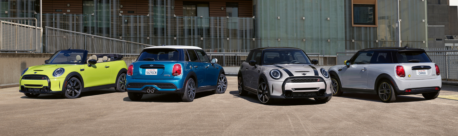 The 2022 MINI Hardtop 2 Door, 2022 MINI Hardtop 4 door, 2022 MINI Hardtop Convertible, and 2022 MINI Electric Hardtop 2 Door parked in a courtyard.