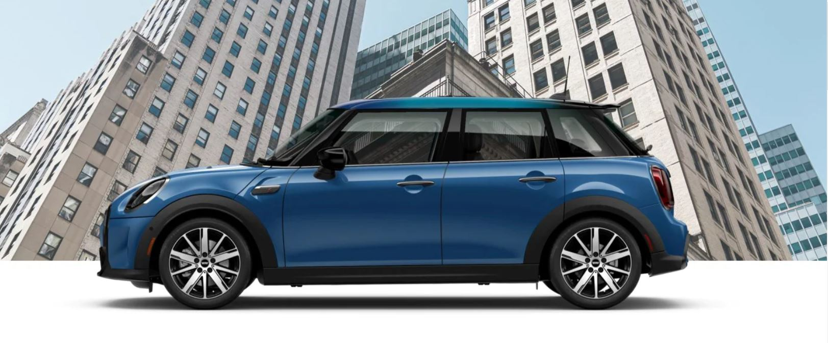 MINI The 2022 MINI Hardtop 4 Door parked in front of a 3D geometric background.