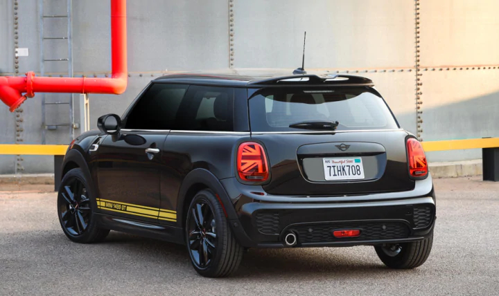 A rear view The MINI Cooper 1499 GT Special Edition parked in front of a garage.