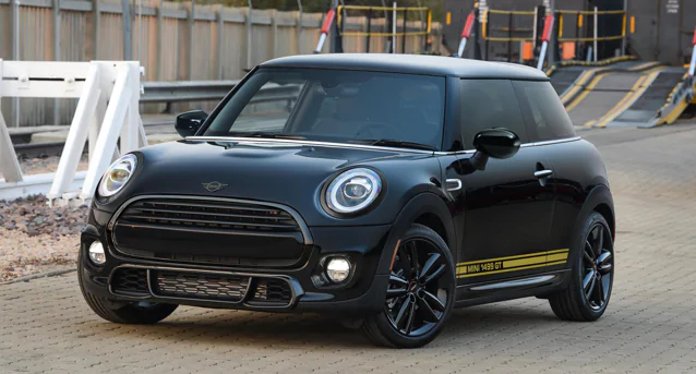 The MINI Cooper 1499 GT Special Edition driving by a construction site.