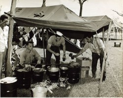 A black and white image of people under a tent.