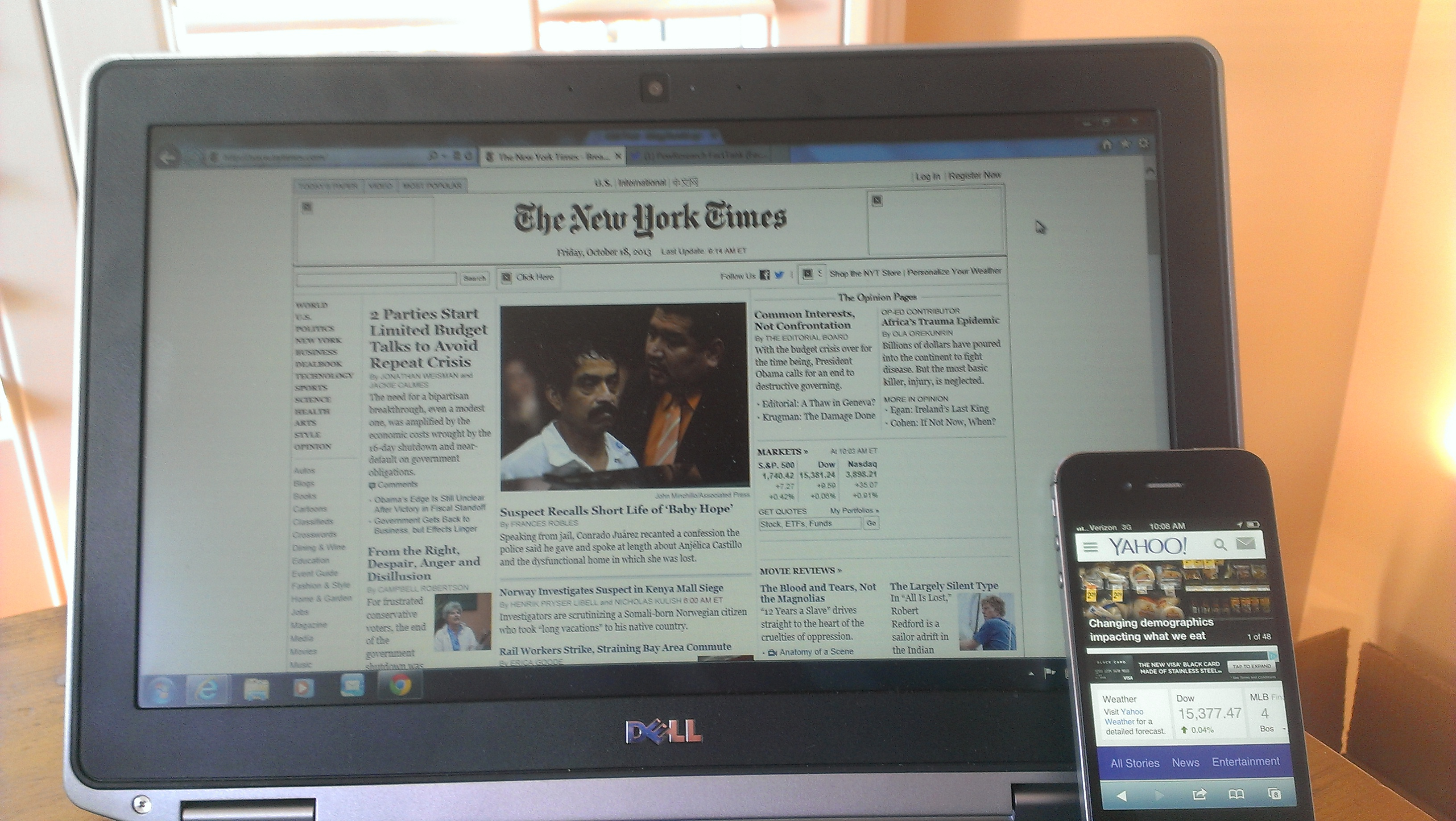 Laptop screen showing homepage of New York Times, and a smartphone showing Yahoo News page.