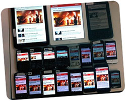 Many smartphones and tablets on a table displaying the same app.