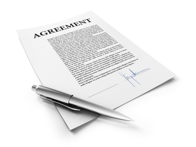 Typed sheet of paper with Agreement and the top and a pen laying on it.