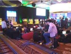 People working on computers in an informal lounge like area at the Top Coder Event.