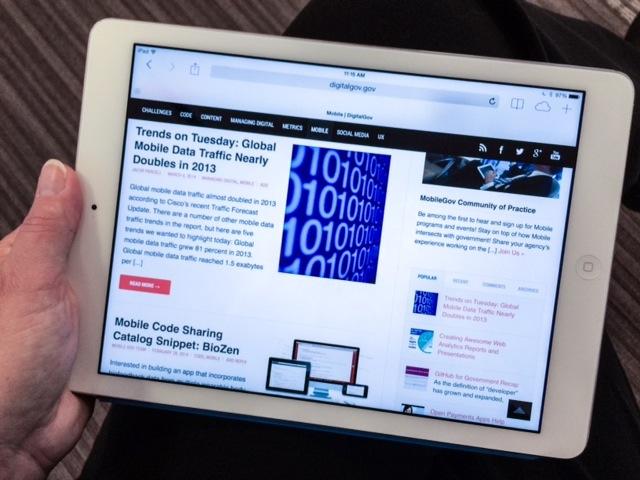 Hand holding tablet screen showing Digitalgov.gov's mobile channel posts.