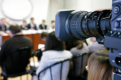 A video camera is positioned behind a crowd of people seated at a public meeting or conference.