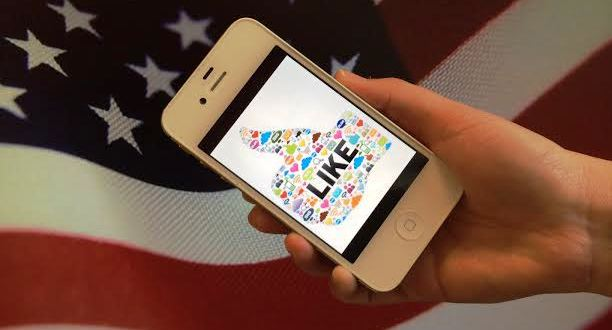 Image of a hand holding phone in front of flag.