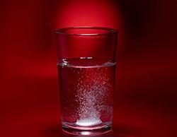 A pill fizzes in a glass