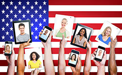 A diverse group of hands hold up various mobile devices, each displaying a person, in front of an American flag