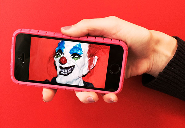 Halloween clown mask seen on a smart phone.