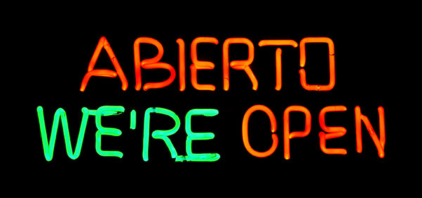 Neon sign that has spanish and English wording for We are open.
