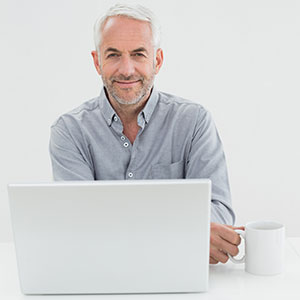 A smiling, mature businessman with laptop and coffee cup.