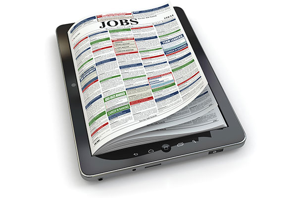 Search jobs on newspaper in tablet. Conceptual image