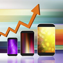 Rising graph arrow shown above different sizes of smartphones that are getting progressively larger, on an abstract, multi-colored background.