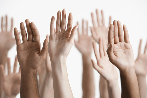 Close-up of raised, multi-ethnic hands.