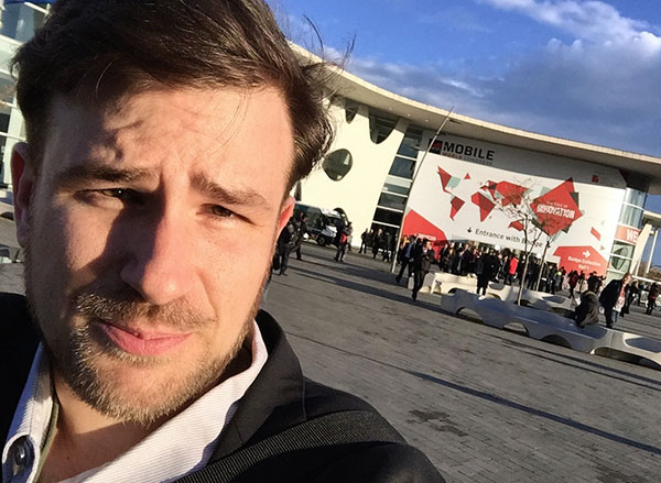 Will Sullivan takes a selfie outside the entrance to the Mobile World Congress