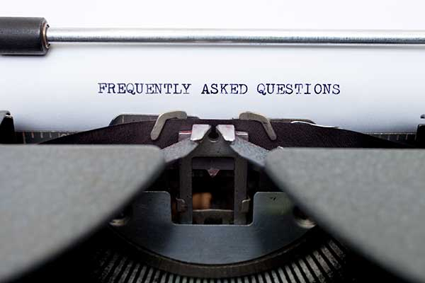 Frequently Asked Questions displays as typed on white paper in an old typewriter.