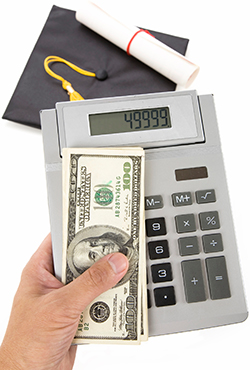 A graduation cap and diploma is seen in the background, with a hand holding a calculator and a stack of hundred dollar bills in the foreground.