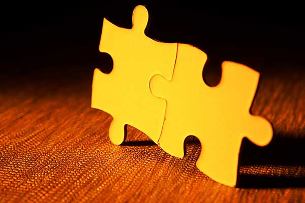 Two yellow puzzle pieces on a wooden table.