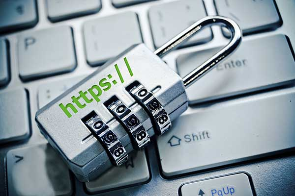 A small metal padlock rests on a keyboard to represent HTTPS; hypertext transfer protocol secure