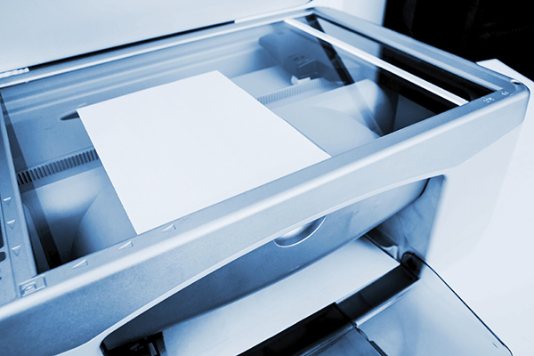 A sheet of paper lies on a copier