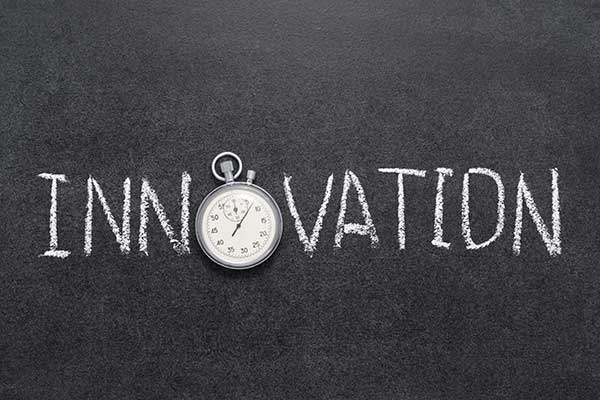 The word Innovation on a chalkboard, with a stop watch for the letter o.