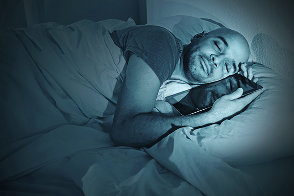 Internet addict in bed sleeping with digital pad or tablet