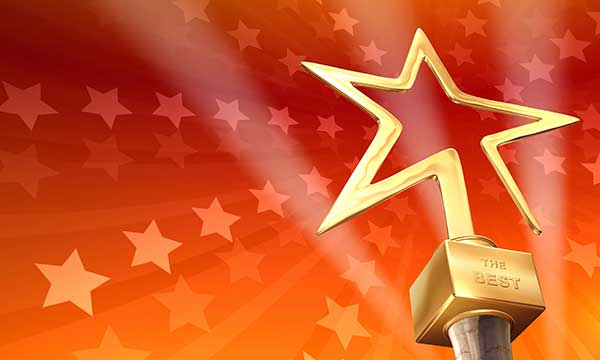 A n award for The Best shaped like a gold star, against a red and gold hued background.