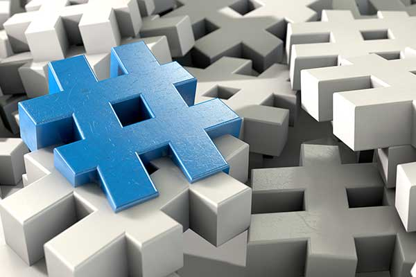 One blue hashtag on a field of white hashtags (pound signs).