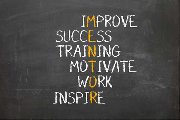 The words Improve, Success, Training, Motivate, Work, and Inspire intersect the word Mentor on a blackboard.