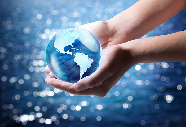 A pair of hands hold a blue globe showing the Western Hemisphere of the Americas, over a background of sparkling water.